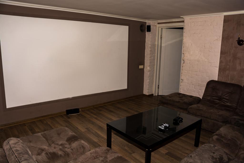 Один из залов Плей бара: проектор, длинный мягкий уголок и столик для напитков